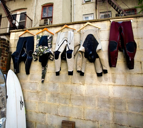 Wet suits hang in the garden at Soho's Saturdays Surf.