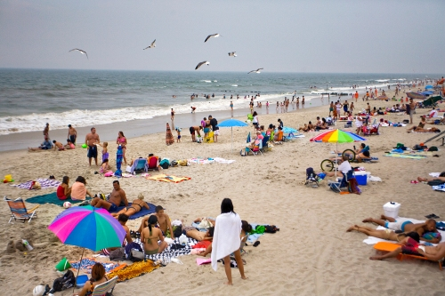 People crowd the beach on a Wednesday afternoon at Rockaway Beach in Queens, New York.