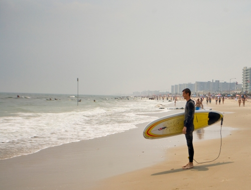 A surfer holds his surf board at Rockaway Beach in Queens, New York