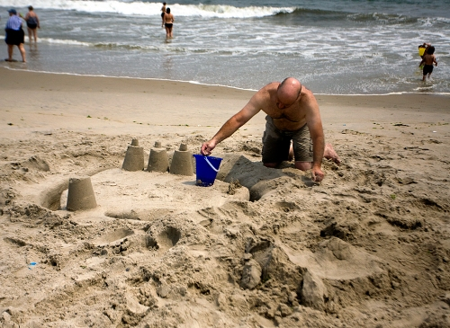 A man builds a sand castle along Rockaway Beach in Queens, New York.